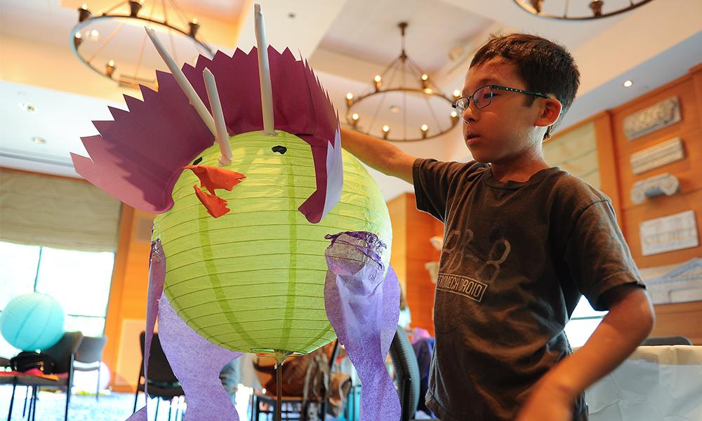 Child holds dinosaur lantern