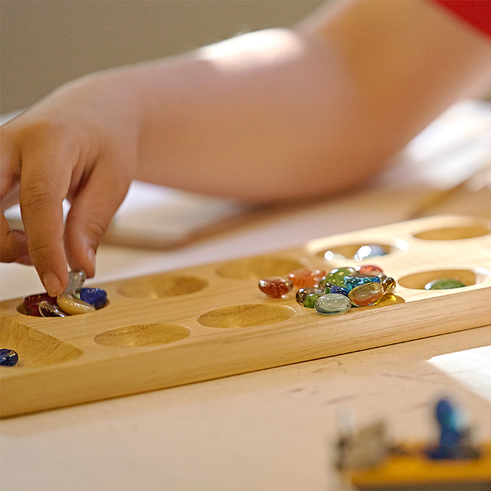 Child plays mancala
