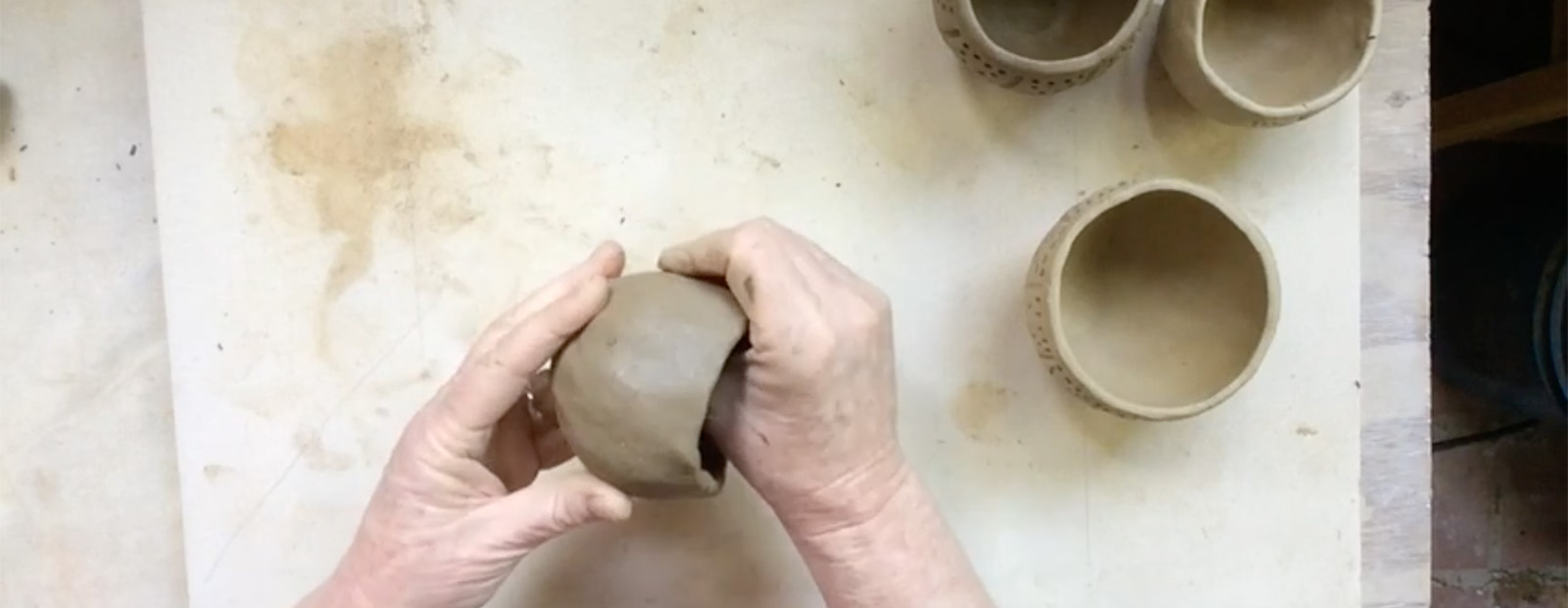 Hands making a pinch pot out of clay