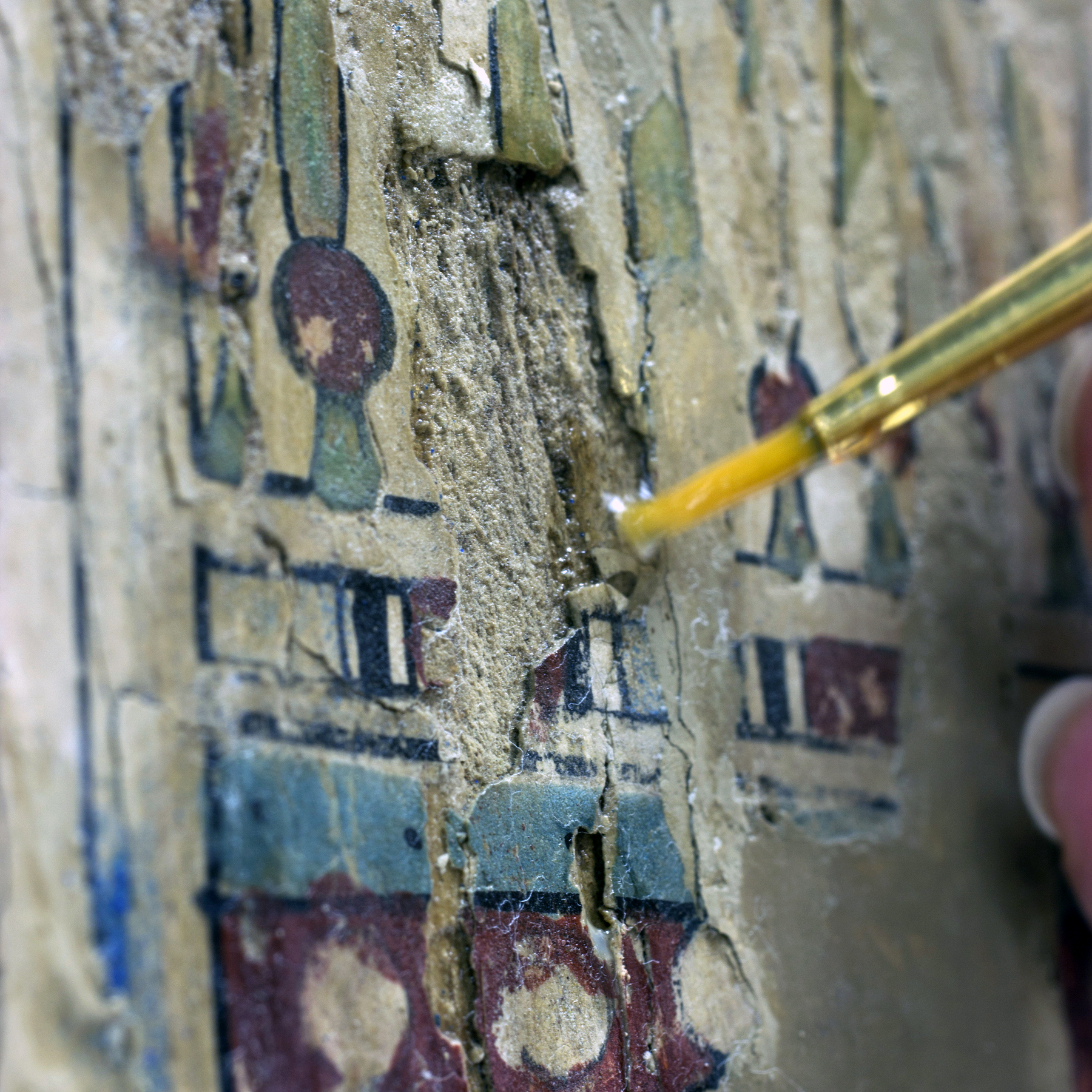 Conservator uses a paintbrush to treat a piece of art
