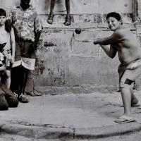 Children play baseball in the street